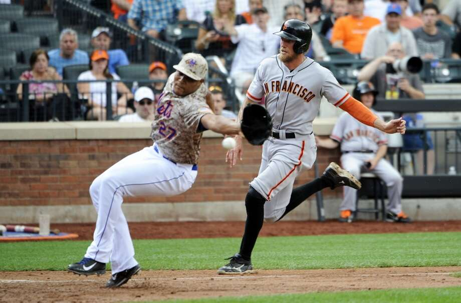 San Francisco Giants' Hunter Pence (8) runs past New York Mets relief pitcher Jeurys Familia (27) to score on a wild pitch in the seventh inning. Photo: Kathy Kmonicek, Associated Press
