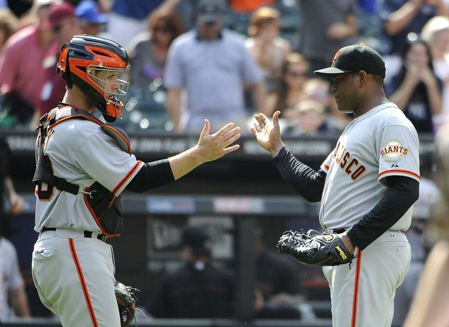 San Francisco Giants catcher Buster Posey congratulates relief pitcher Santiago Casilla after the Giants beat the New York Mets 4-3. Photo: Kathy Kmonicek, Associated Press