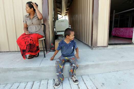 Ingrid Xiomara Alcantara Bram, 28, of Honduras and her son, Juan Jose Maradiaga, 7, wait it out at The Way of Life immigrant shelter in Reynosa, Mexico, Tuesday, July 29, 2014. The shelter currently houses close to 80 men, women and children at the shelter near the Rio Grande. Photo: Jerry Lara, San Antonio Express-News / @San Antonio Express-News