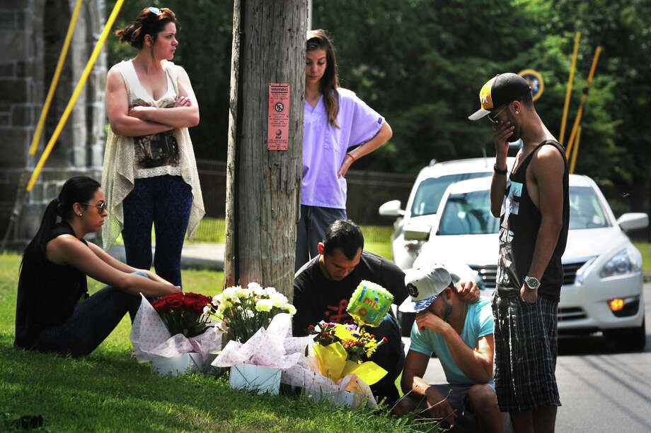 Friends and relatives gather at the base of a utility pole on North Ave., in Bridgeport, Conn. where Arthur De Andrade Leao died when he crashed his motorcycle early Sunday morning. Photo: Ned Gerard / Connecticut Post