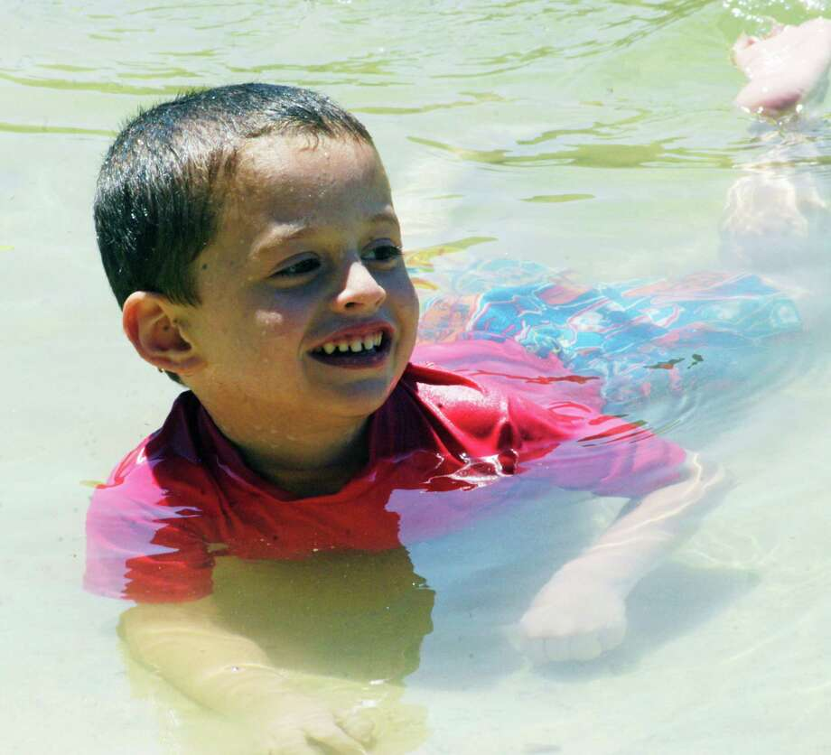 Daniel Nichols, 4, of New Milford frolicks in the warm waters of Candlewood Lake while spending a day at Lynn Deming Park with his family. July 2014 Photo: Norm Cummings / The News-Times