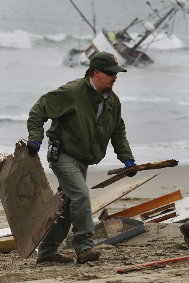 Workers remove debris from the shoreline after a fishing boat abandoned by its owner washed up on Ocean Beach across from the Beach Chalet on August 04, 2014 in San Francisco, CA. The owner is currently missing. Photo: Craig Hudson, The Chronicle