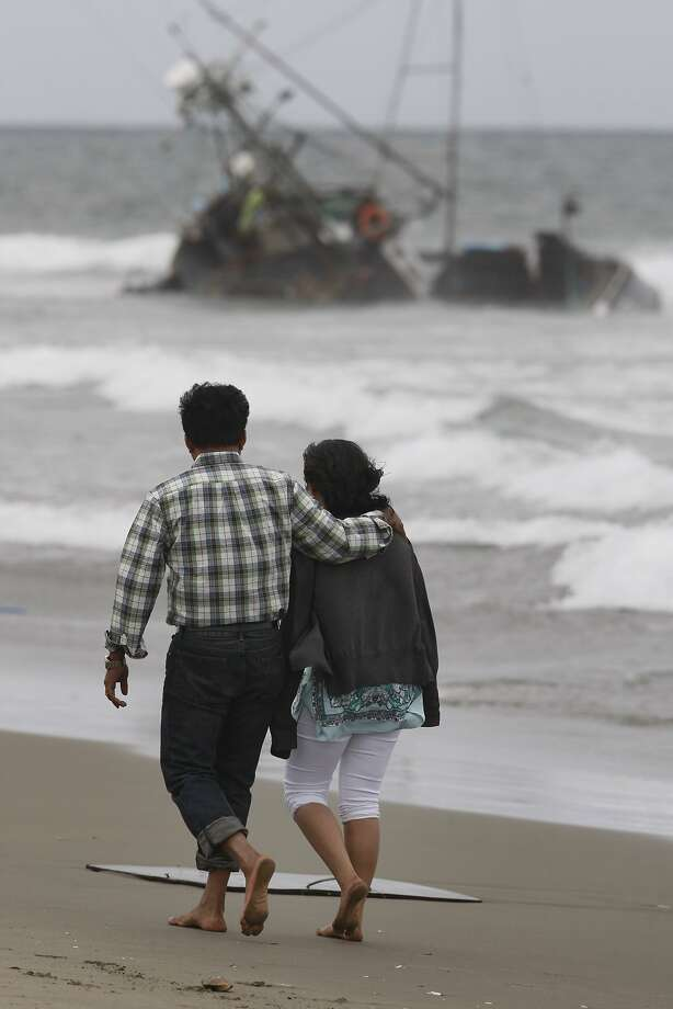 A couple walk past a fishing boat that washed up on Ocean Beach across from the Beach Chalet on August 04, 2014 in San Francisco, CA. The owner is currently missing. Photo: Craig Hudson, The Chronicle