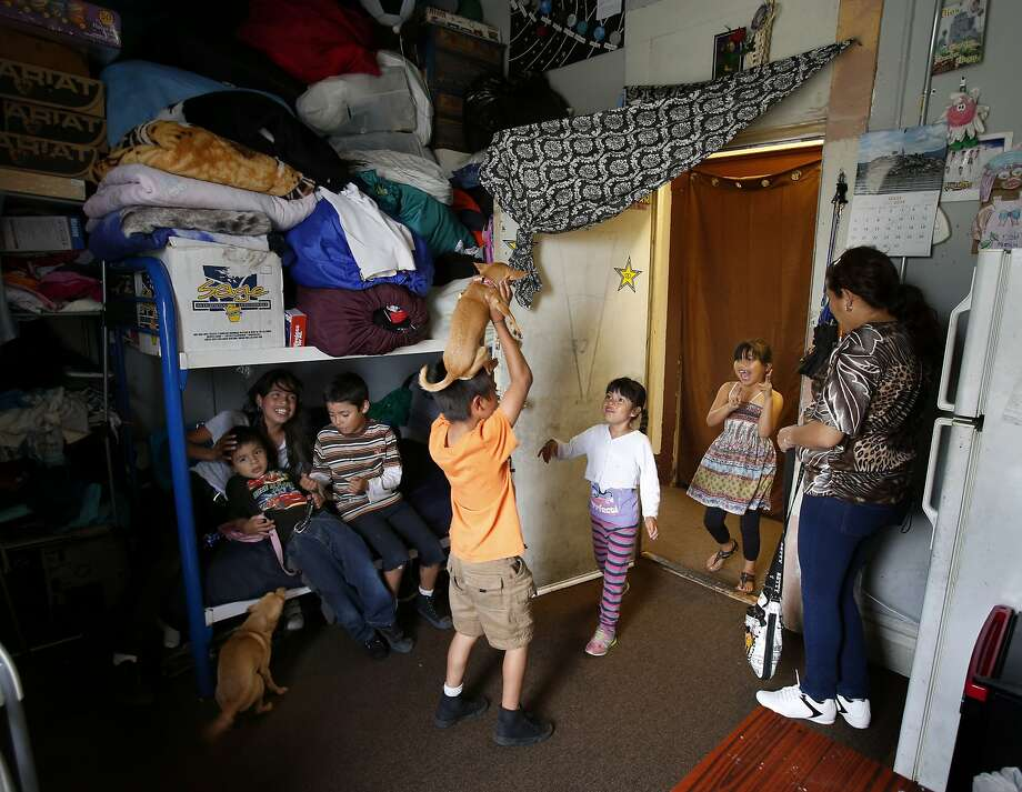 In their small living space, Laura Chinas and her children play with their dogs along with others who live in the building. The single room occupancy hotel on Mission Street has a history of complaints from residents. Photo: Brant Ward, San Francisco Chronicle