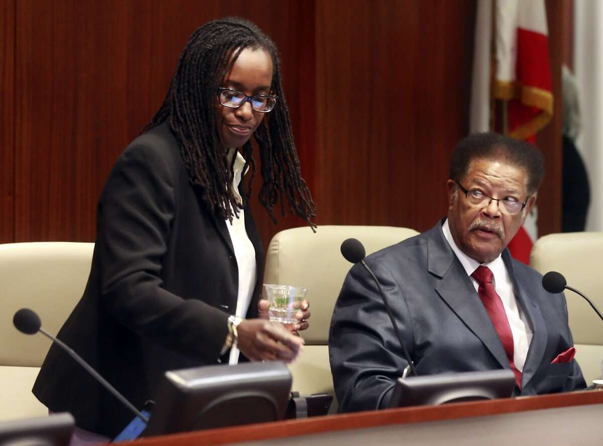 Vice Mayor Jovanka Beckles, left, returns to her seat next to councilmember Nathaniel Bates, right, at the Richmond City Council meeting in Richmond, Calif., on Tuesday, July 15, 2014. Jovanka Beckles, a Richmond city councilmember who is a lesbian and native of Panama, has been hounded mercilessly by a few members on the council and their constituents in the audience. The behavior has prompted the council to explore a potential 6-month ban on audience members who disrupt the proceedings.
