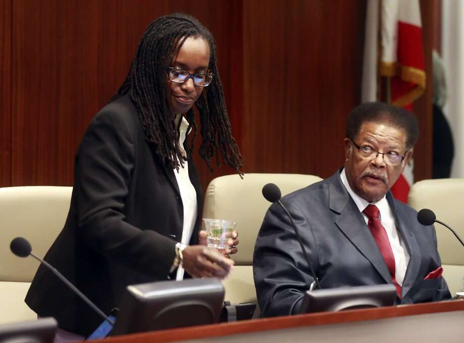 Vice Mayor Jovanka Beckles, left, returns to her seat next to councilmember Nathaniel Bates, right, at the Richmond City Council meeting in Richmond, Calif., on Tuesday, July 15, 2014. Jovanka Beckles, a Richmond city councilmember who is a lesbian and native of Panama, has been hounded mercilessly by a few members on the council and their constituents in the audience. The behavior has prompted the council to explore a potential 6-month ban on audience members who disrupt the proceedings. Photo: Carlos Avila Gonzalez, The Chronicle