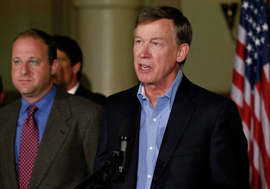 Colo. Gov. John Hickenlooper, right, speaks as U.S. Rep. Jared Polis, D-Colo., left, stands nearby, during a news conference about fracking, at the Capitol in Denver, Monday Aug. 4, 2014. Hickenlooper urged those pushing dueling proposals on oil and gas drilling to stop their campaigns to avoid a messy ballot fight. (AP Photo/Brennan Linsley) Photo: Brennan Linsley, STF / AP