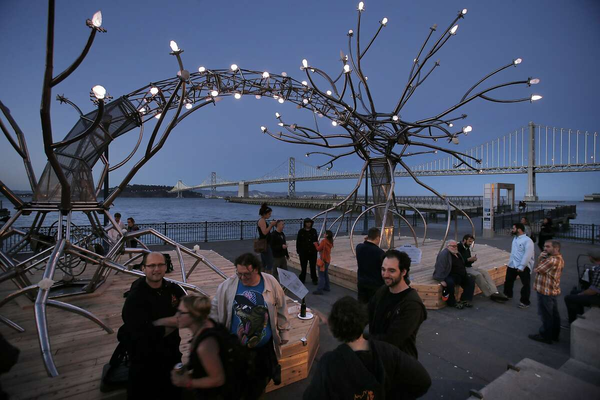 Family and friends of the Flaming Lotus Girls gather around the sculpture SOMA on Wednesday. A new steel sculpture called
