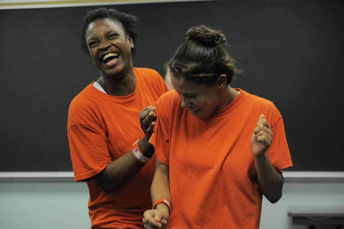 """Inmates Erica Jones, left, and Marisabela Sarria dance during a """"ecstatic"""" dance class led by teacher Sylvie Minot at the San Francisco County Jail on July 17, 2014 in San Francisco, CA. Sylvie Minot leads dance classes inside the SF County Jail to help bring inmates inner peace. Minot also leads classes for the public in Marin, and for vets at the VA clinic."""
