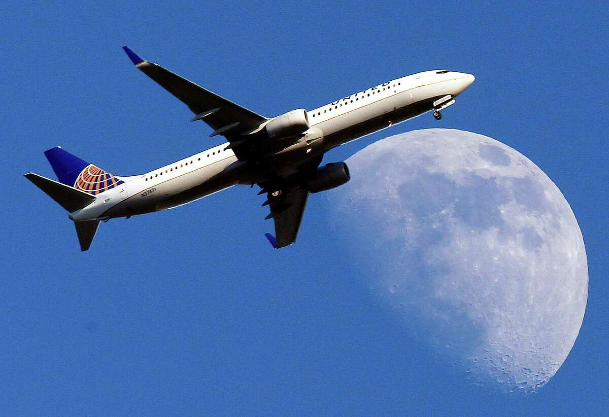 FILE - In this July 17, 2013 file photo, a United Airlines jet approaching Los Angeles International Airport passes in front of a Waxing Gibbous moon. Airfare is up 10.7 percent in the past five years _ after adjusting for inflation _ according to an Associated Press analysis of data from the Airlines Reporting Corp., which processes ticket transactions for airlines and more than 9,400 travel agencies, including websites such as Expedia and Orbitz. ( AP Photo/Nick Ut, File) ORG XMIT: NYBZ107