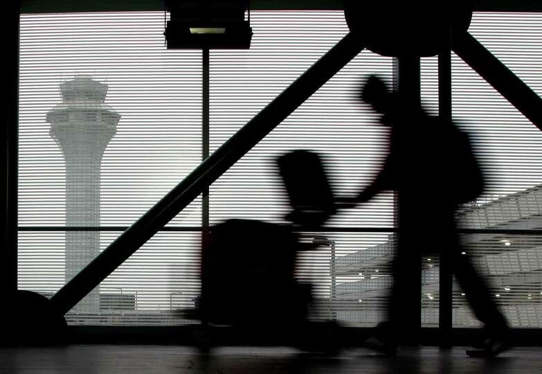 FILE - In this Dec. 21, 2013 file photo, a traveler walks through Terminal 3 at O'Hare International
