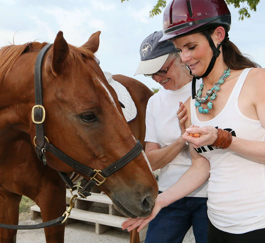 Sabrina McCoy (right) feeds carrots to Mr. Cool, a thoroughbred she rides for therapy. Assisting is Kerstin Fosdick of the Saddle Light Center. Photo: Photos By Marvin Pfeiffer / Northeast Herald / EN Communities 2014