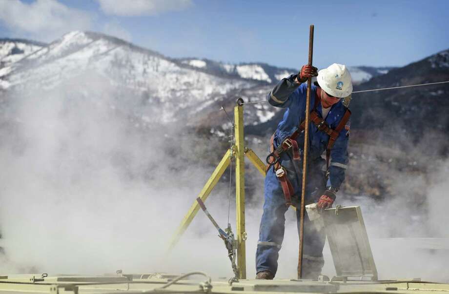 A worker checks a  hydraulic fracturing site in Colorado.  Lawmakers there have averted a fracking ballot measure in November. Photo: Associated Press File Photo / AP