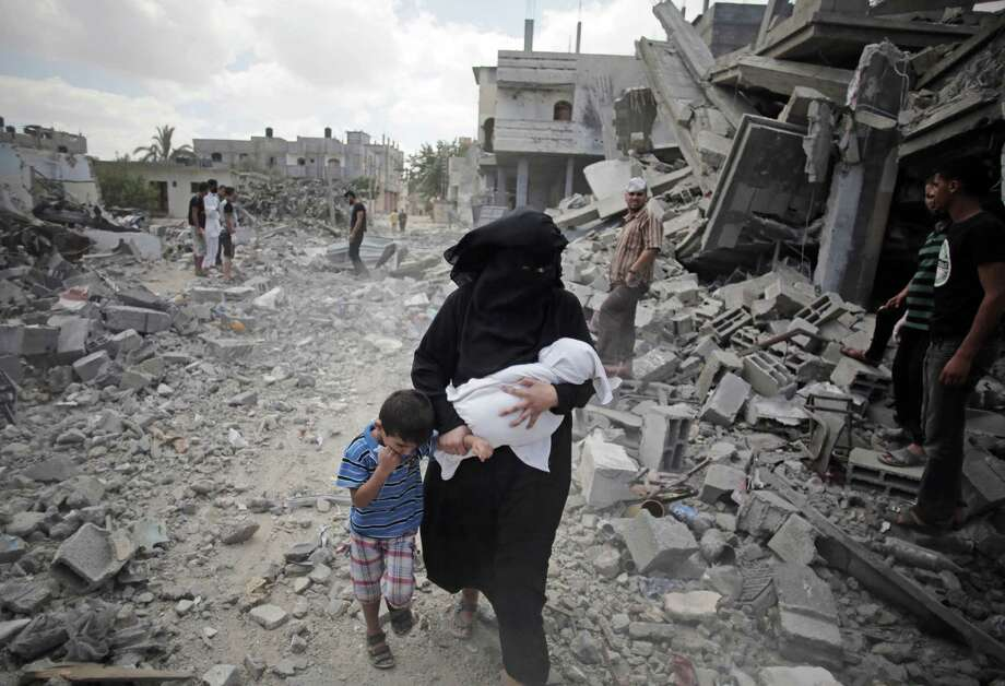 A Palestinian woman passes by rescuers inspecting the rubble of destroyed houses following Israeli strikes in Rafah refugee camp, southern Gaza Strip, Monday, Aug. 4, 2014. (AP Photo/Khalil Hamra) Photo: Khalil Hamra, STF / AP