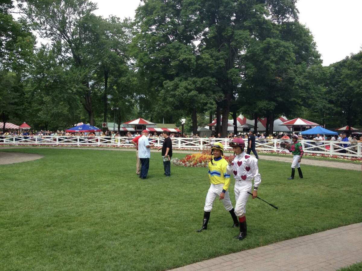 The jockeys, well, some of them, head to the paddock before the second race at Saratoga on Monday. That's Jose Lezcano in the yellow, John Velazquez with the hearts and Andre Shivnarine Worrie bringing up the rear. Lezcano won the race, guiding favored Greg's Intuition to the winner's circle. Greg's Intuition paid $7.40 to win. (Tim Wilkin / Times Union)