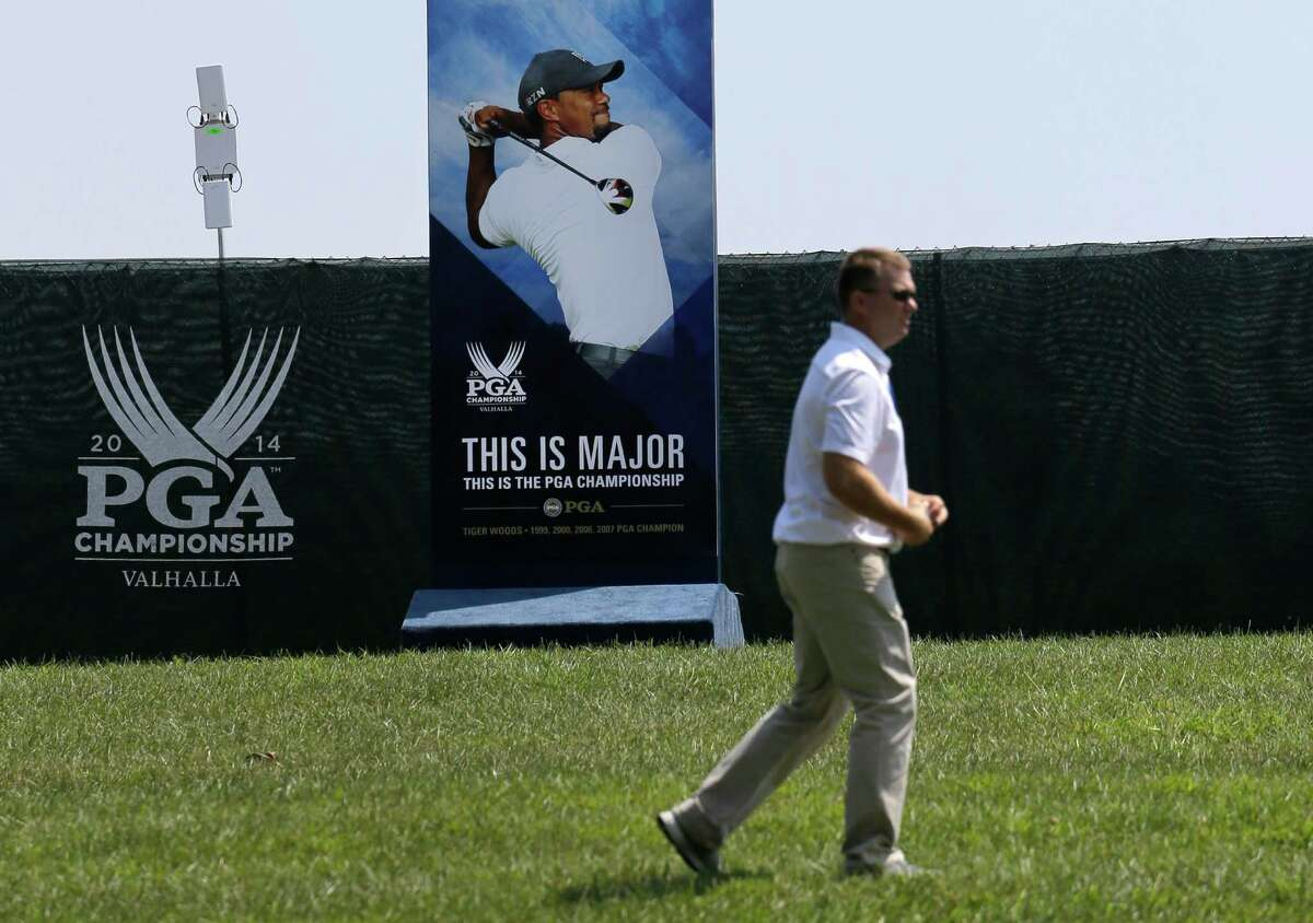 A man walks past a photo of golfer Tiger Woods at the PGA Championship golf tournament at Valhalla Golf Club Monday, Aug. 4, 2014, in Louisville, Ky. Whether Woods will play in the tournament, which is set to begin on Thursday, is unclear after he suffered a setback Sunday when he was stricken with back pain and withdrew after eight holes from the Bridgestone Invitational. (AP Photo/Jeff Roberson) ORG XMIT: KYJR106