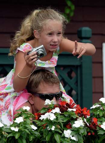 Anei Taylor, 8, of Nashua, N.H., tries to find her horse in the second race while sitting on her father's, Stephen, shoulders Monday afternoon, Aug. 5, 2014, at  Saratoga Race Course in Saratoga Springs, N.Y.   (Skip Dickstein/Times Union) Photo: SKIP DICKSTEIN