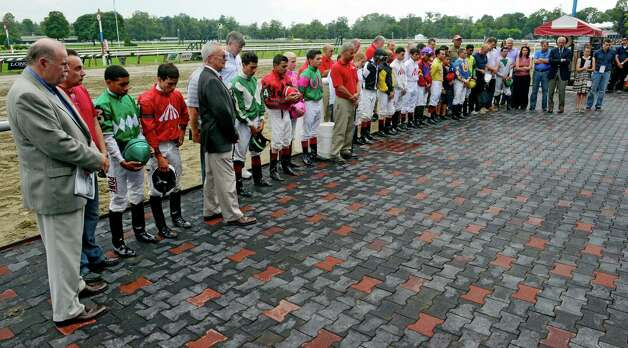 The jockey colony and others observe a moment of silence in the winner's circle for the lose of trainer Alan Jerken's wife Elizabeth Monday, Aug. 5, 2014, at Saratoga Race Course in Saratoga Springs, N.Y. She passed away early Monday morning in Florida. (Skip Dickstein/Times Union) Photo: SKIP DICKSTEIN