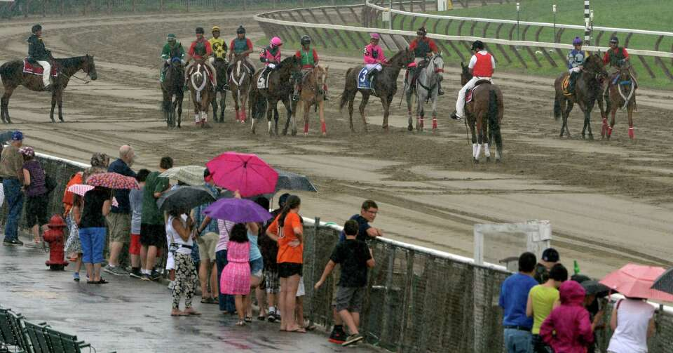 Horses gather for the third race during a rain shower Monday afternoon, Aug. 5, 2014, at  Saratoga R