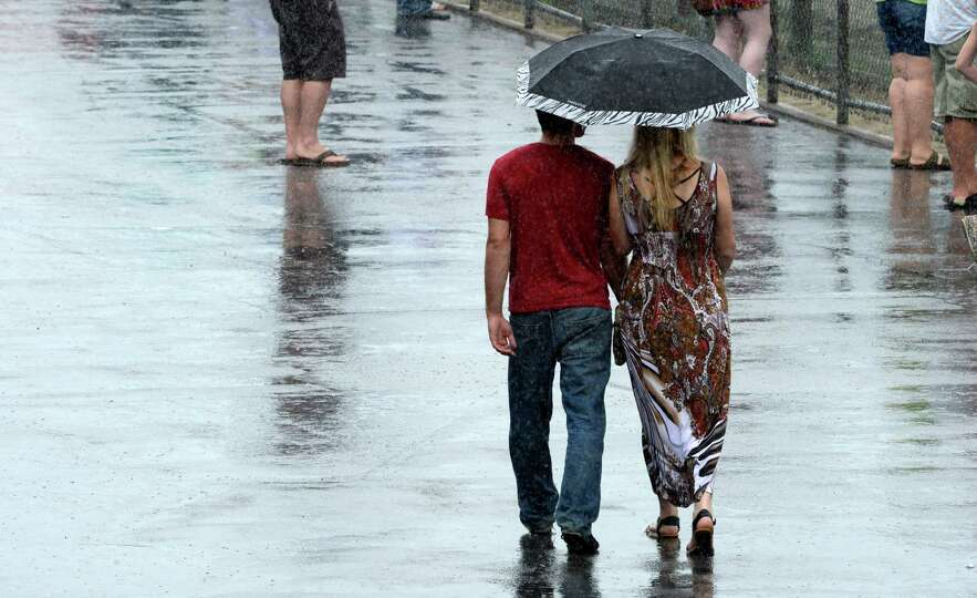 A couple huddles under an umbrella during a brief shower Monday afternoon, Aug. 5, 2014, at  Saratog