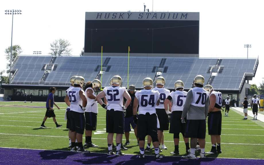 Washington's offensive linemen huddle near the end zone of Husky Stadium during the Huskies' first practice of fall camp on Monday at Husky Stadium. Photo: Ted S. Warren, AP
