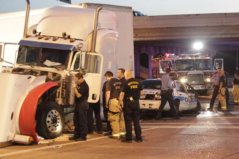 A Houston police squad car and a tractor-trailer were involved in a wreck about 7:30 p.m. Monday, with three frontage road lanes closed on northbound Interstate 45 at Cavalcade. Photo: Johnny Hanson / Houston Chronicle