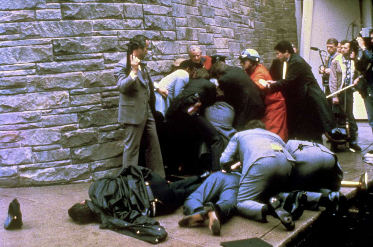 FILE - This March 30, 1981 file photo shows a U.S. secret service agent with an automatic weapon watches over James Brady, the president's secretary, after being wounded in an attempt on the life of President Ronald Reagan in Washington. A Washington, D.C. policeman, Thomas Delahanty, lies to the left after also being shot. A Brady family spokeswoman says Brady has died at 73. (AP Photo/Ron Edmonds) ORG XMIT: WX304