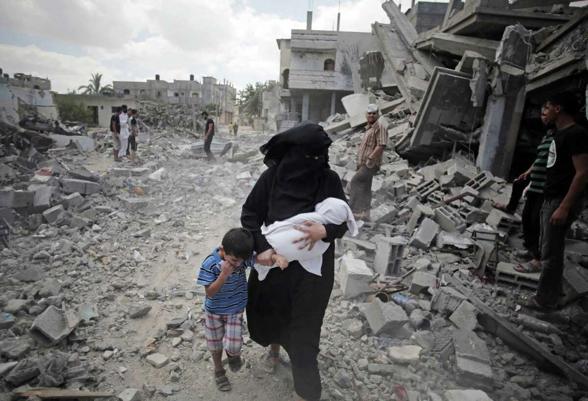 A Palestinian woman passes by rescuers inspecting the rubble of destroyed houses following Israeli strikes in Rafah refugee camp, southern Gaza Strip, Monday, Aug. 4, 2014. (AP Photo/Khalil Hamra) ORG XMIT: KH112
