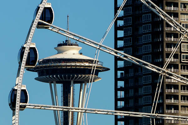 The Space Needle peeks from between the pods of Seattle's Great Wheel Monday, August 4, 2014, in Seattle, Wash.