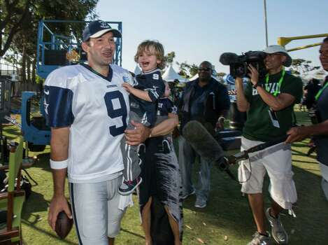 Dallas Cowboys quarterback Tony Romo (9) plays with his son, Hawkins at the end of practice at NFL football training camp, Thursday, July 31, 2014, in Oxnard, Calif. (AP Photo/Ringo H.W. Chiu) Photo: Associated Press / FR170512 AP
