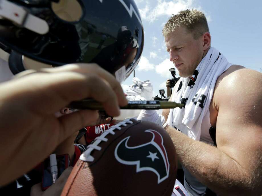 Texans defensive end J.J. Watt, signing autographs, is being lauded for the way he goes about his business. Photo: David J. Phillip / Associated Press / AP