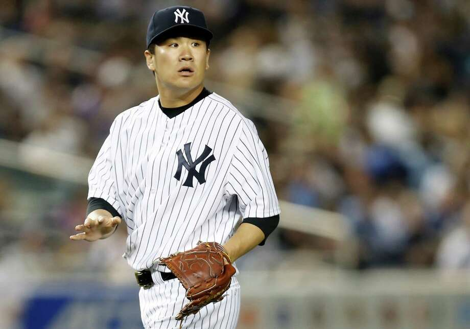 New York Yankees starting pitcher Masahiro Tanaka (19) reacts after a teammate checks on him to see if he was grazed by a ground ball in the sixth inning of a baseball game against the Toronto Blue Jays at Yankee Stadium in New York, Tuesday, June 17, 2014.  (AP Photo/Kathy Willens) Photo: Kathy Willens, STF / AP