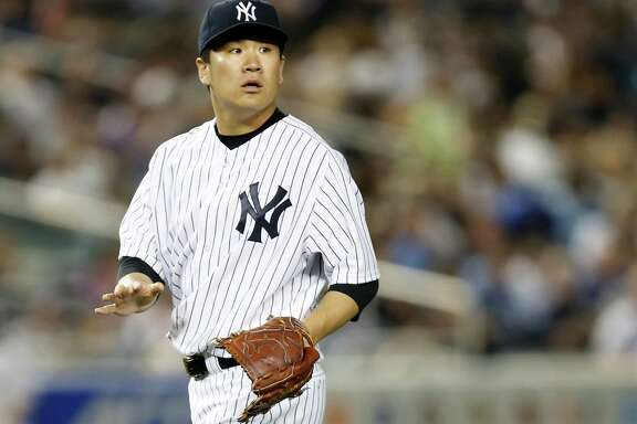 New York Yankees starting pitcher Masahiro Tanaka (19) reacts after a teammate checks on him to see if he was grazed by a ground ball in the sixth inning of a baseball game against the Toronto Blue Jays at Yankee Stadium in New York, Tuesday, June 17, 2014.  (AP Photo/Kathy Willens)