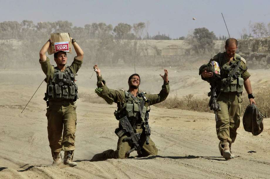 An Israeli soldier gestures in relief as he travels with comrades near the border between Israel and the Gaza Strip after returning from the Hamas-controlled Palestinian coastal enclave. Photo: Gil Cohen-Magen / Getty Images / AFP