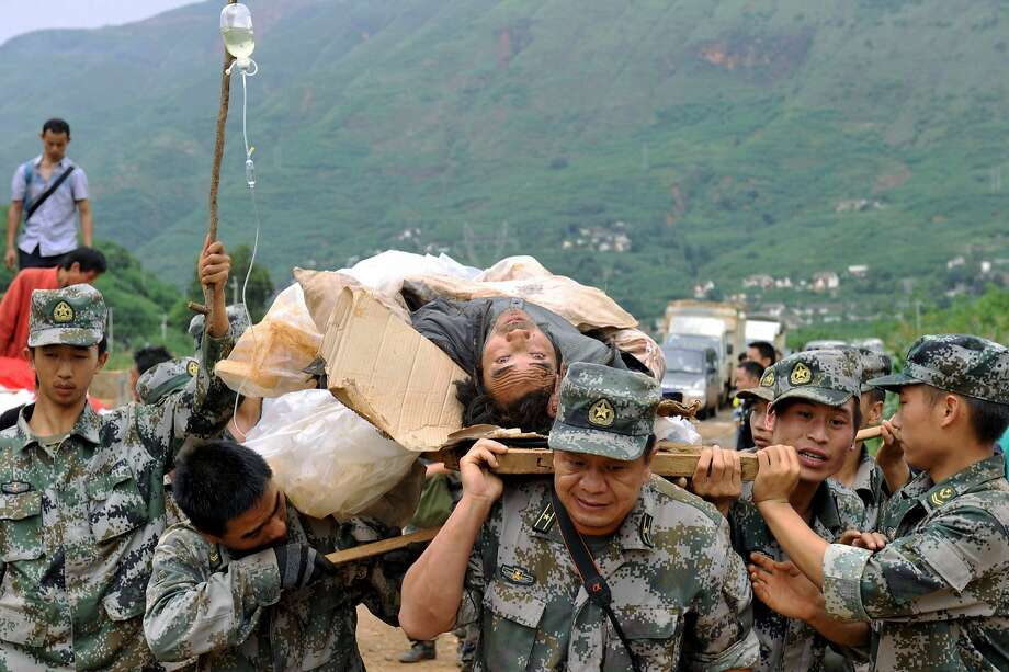 Rescuers carry an injured man during a rescue operation following Sunday's earthquake in Ludian county of Zhaotong city in southwest China's Yunnan Province, Monday, Aug. 4, 2014. Rescuers dug through shattered homes Monday looking for survivors of the strong earthquake that killed hundreds and injured more than a thousand people. (AP Photo/Kyodo News) JAPAN OUT Photo: Uncredited, Associated Press