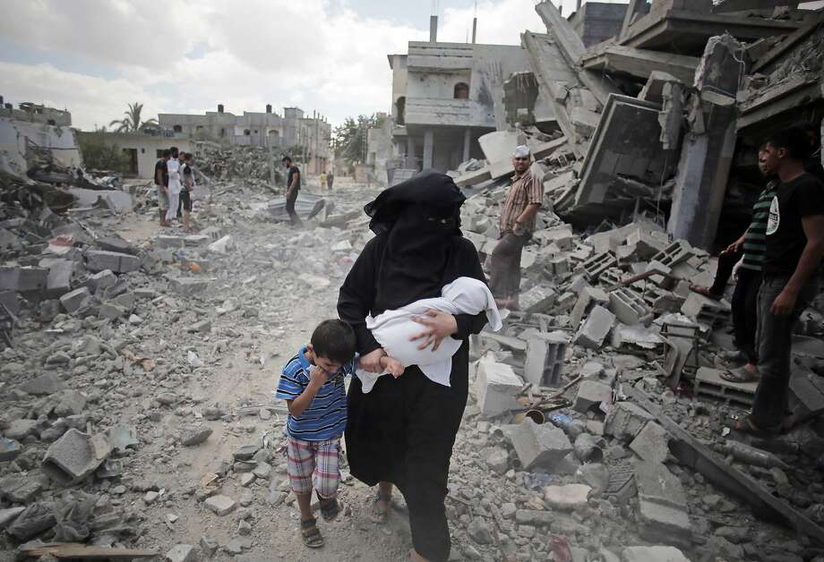 A Palestinian woman passes by rescuers inspecting the rubble of destroyed houses following Israeli strikes in Rafah refugee camp, southern Gaza Strip, Monday, Aug. 4, 2014. (AP Photo/Khalil Hamra) Photo: Khalil Hamra, Associated Press