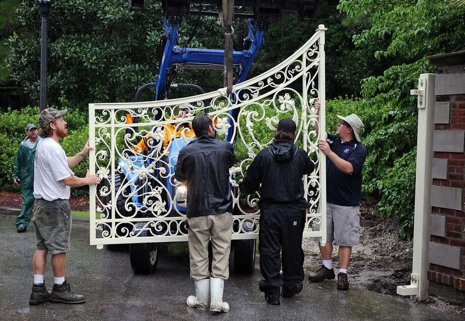 Blacksmith Ben Kastner, with Intracoastal Iron & Metalwork, left, oversees the installation of the restored gate at Airlie Gardens in Wilmington, N.C., Monday, Aug. 4, 2014. Intracoastal Iron & Metalwork restored the gate that was constructed in France in the late 1700s or early 1800s and originally installed at the entrance to Airlie Gardens in 1920. (AP Photo/The Star-News, Mike Spencer) Photo: Mike Spencer, Associated Press