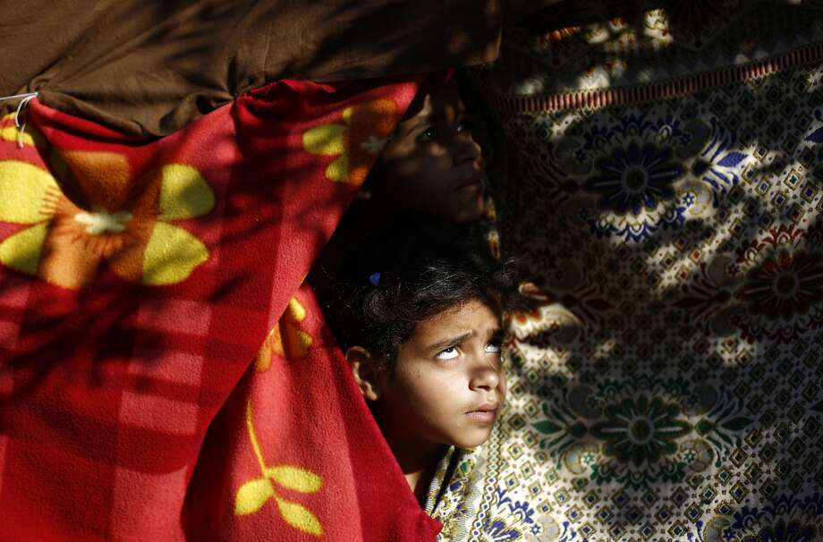 """TOPSHOTS A displaced Palestinian child looks out from a tent where his family are taking refuge in Beit Lahia in the northern Gaza Strip on August 4, 2014, after fleeing their home due to Israeli shelling on the besieged Palestinian Territory. Israel will hold its fire in most of the Gaza Strip for a seven-hour """"humanitarian window"""", the military said, four weeks into its bloody conflict with Hamas. AFP PHOTO/ MOHAMMED ABEDMOHAMMED ABED/AFP/Getty Images Photo: Mohammed Abed, AFP/Getty Images"""
