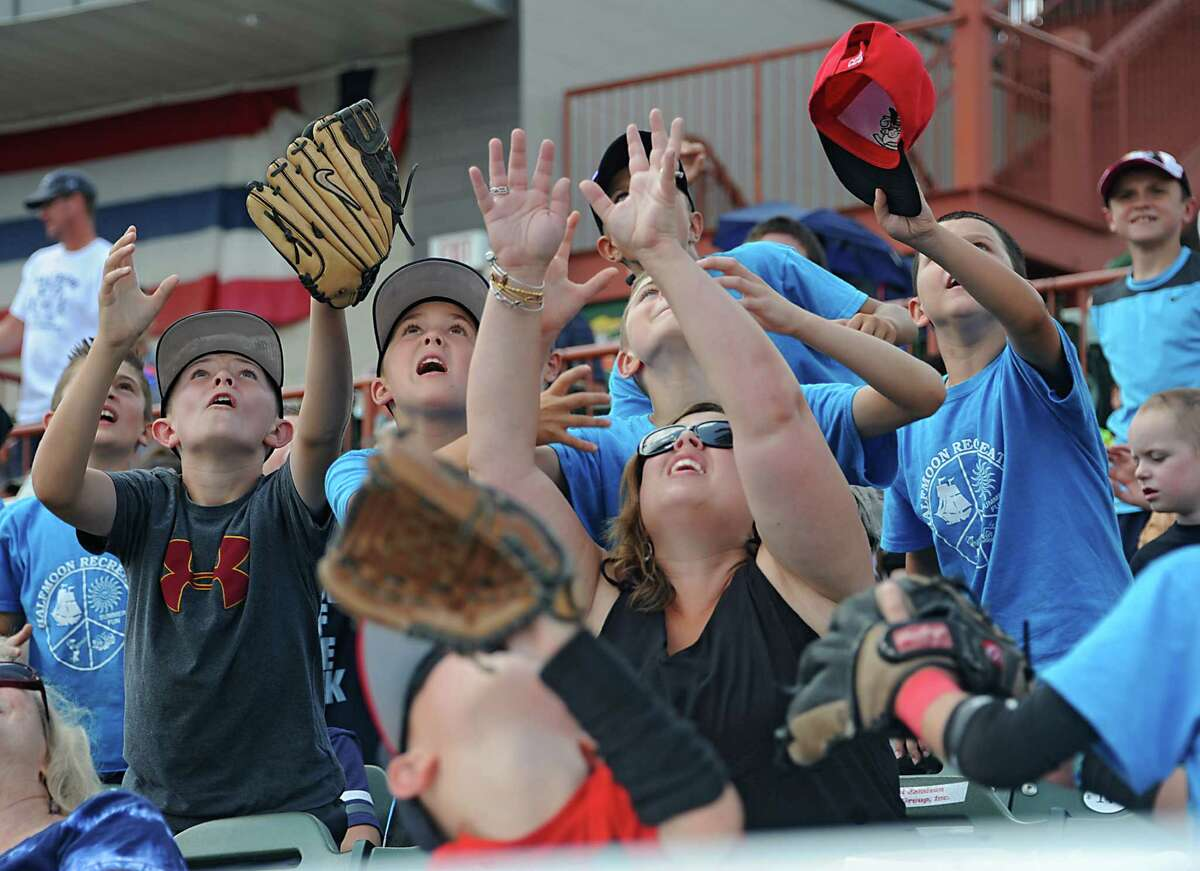 Tri-City ValleyCats fan Aidan Ryan, 10, of Clifton Park, left, ends up catching a ball thrown into the stands during a baseball game against the Batavia Muckdogs at the Joe Bruno Stadium on Monday, Aug. 4, 2014 in Troy, N.Y. Aidan was watching the game with the Halfmoon Recreation camp. (Lori Van Buren / Times Union) ORG XMIT: MER2014080507512502