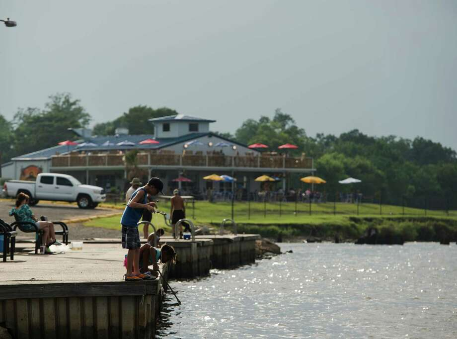 Adam Leboeuf, 10, Shayla Boland, 9, and others fish off a dock on the Neches River on Friday afternoon. The Port Neches City Council is discussing how to market the city's riverfront area, the main attractions of which are currently Port Neches Park and the new Neches River Wheelhouse restaurant. Photo taken Friday 8/1/14 Jake Daniels/@JakeD_in_SETX Photo: Jake Daniels / ©2014 The Beaumont Enterprise/Jake Daniels