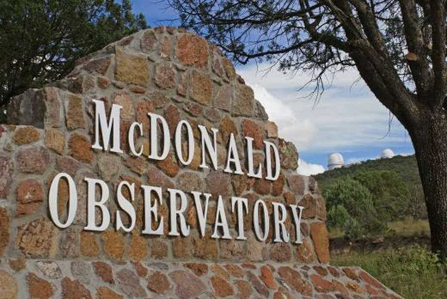 The entrance to the McDonald Observatory, founded in the 1930s in the Davis Mountains, is shown with two telescopes in the background. Light pollution from development in West Texas and the Permian Basin region are making stargazing difficult. Photo: Frank Cianciolo