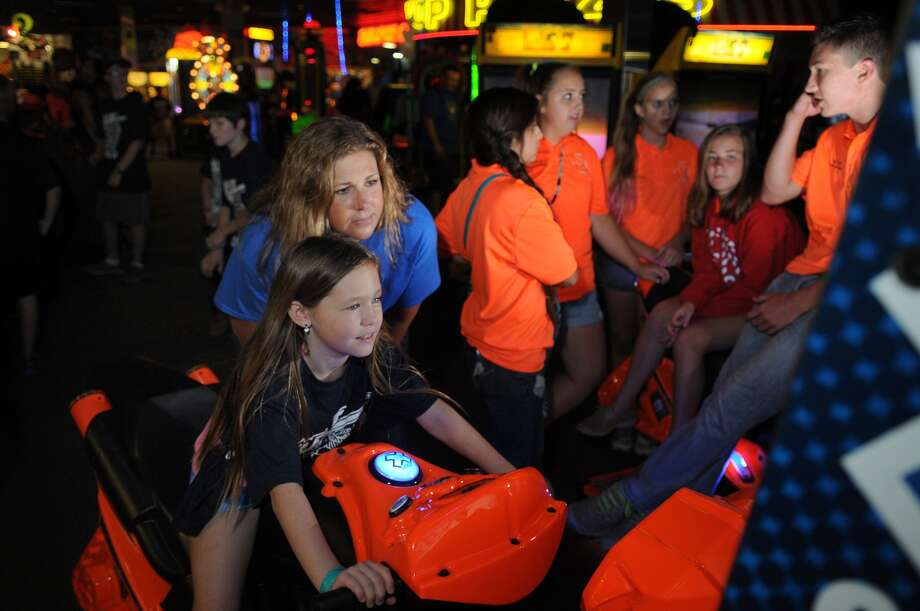 Abby Thompson, 8, left, a third-grader at Oak Ridge Elementary, shows off her Snocross riding skills to CISD Police Department Sgt. Julie Wright at Incredible Pizza in Conroe. Photo: Jerry Baker, Freelance