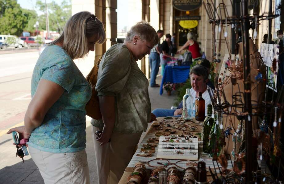 Christine Balentine, front, and Helen Sohlinger browse the wares at the B. Marie Sea Glass Jewelry booth Thursday afternoon. The sidewalks along the Mildred Building were dotted with vendors, shoppers, and musicians during First Thursday on June 5. Cheap vendors spots are available along the sidewalk of Calder Avenue during the monthly event, and live music is accompanied by food and drink. Photo taken Thursday 6/5/14 Jake Daniels/@JakeD_in_SETX
