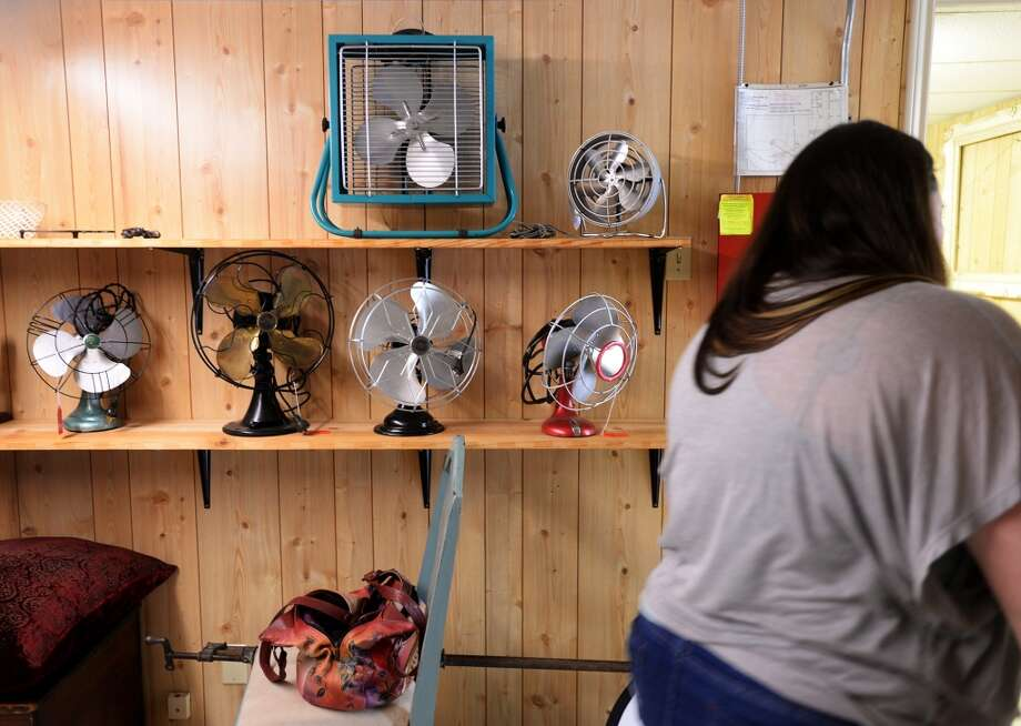 Jennifer Trenbeath walks by a wall of restored fans at Grandma's Basement on Thursday afternoon. Grandma's Basement, a new store specializing in antiques and resale goods, will open for business Saturday, March 22, 2014. Photo taken Thursday, 3/20/14 Jake Daniels/@JakeD_in_SETX