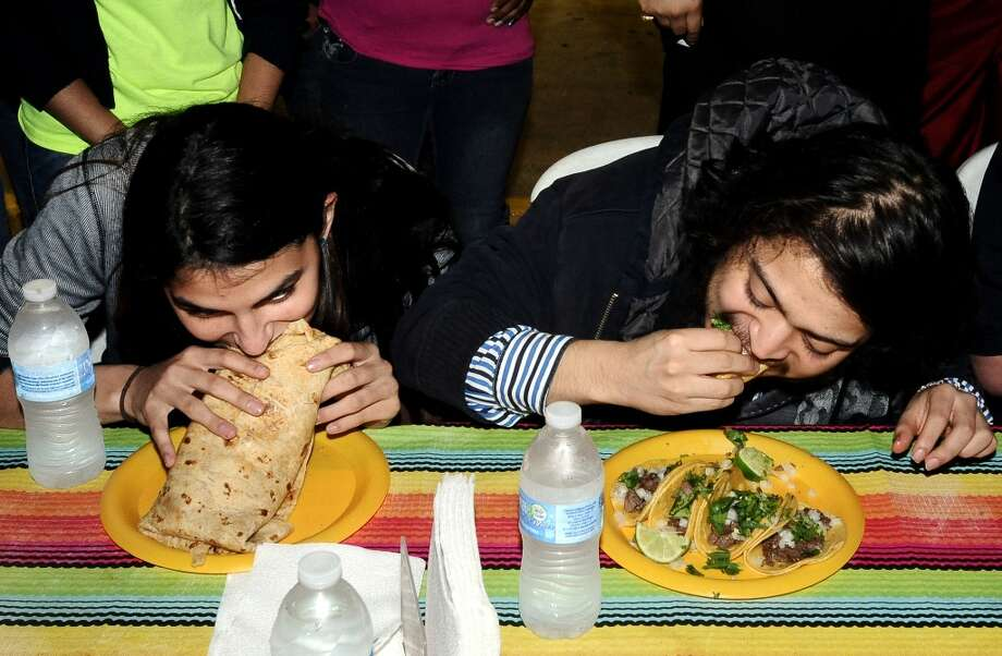 Alanie Padia, left, and Alex Alejandro Avila, right, compete in the couples eating contest at Tacos La Bama's First Thursday event on Thursday, February 7, 2013. Photo taken: Randy Edwards/The Enterprise