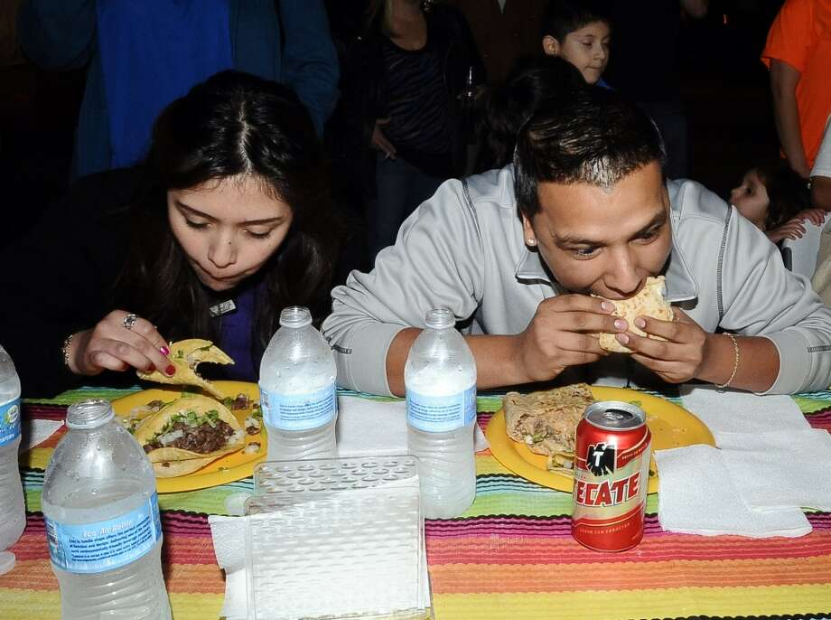 Cricthian Herrera, left, and Daniel Romero, right, compete in the couples eating contest at Tacos La Bama's First Thursday event on Thursday, February 7, 2013. Photo taken: Randy Edwards/The Enterprise