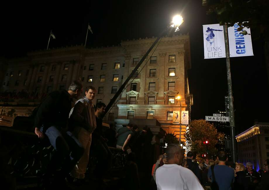 Below a set of movie prop street light banners, people stand along California during filming of Terminator: Genesis in San Francisco, Calif. on Monday, August 4, 2014. Photo: Scott Strazzante, The Chronicle
