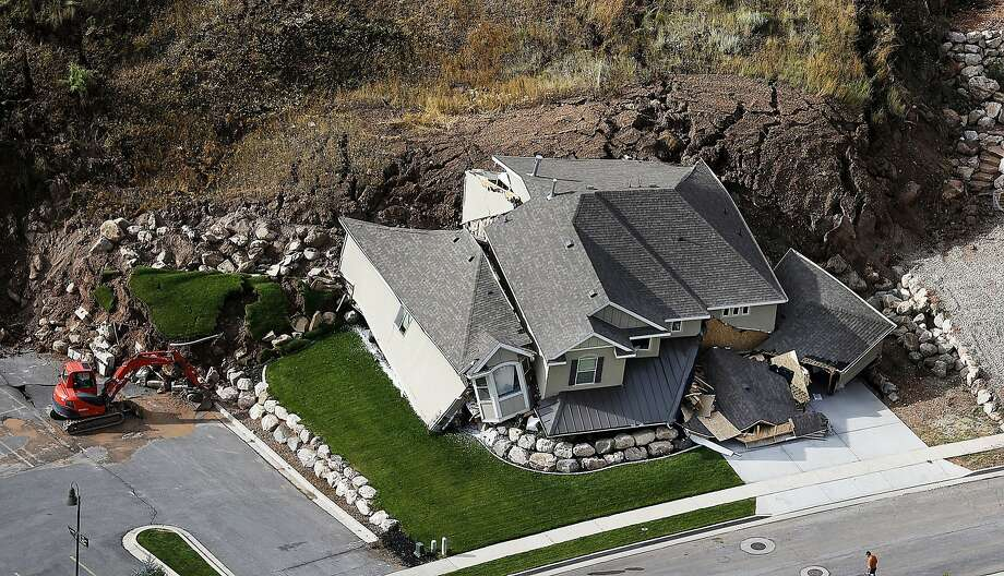 House wrecker: Nobody was injured when rain-soaked earth slid in North Salt Lake, Utah, destroying this home in a hillside community. At least 27