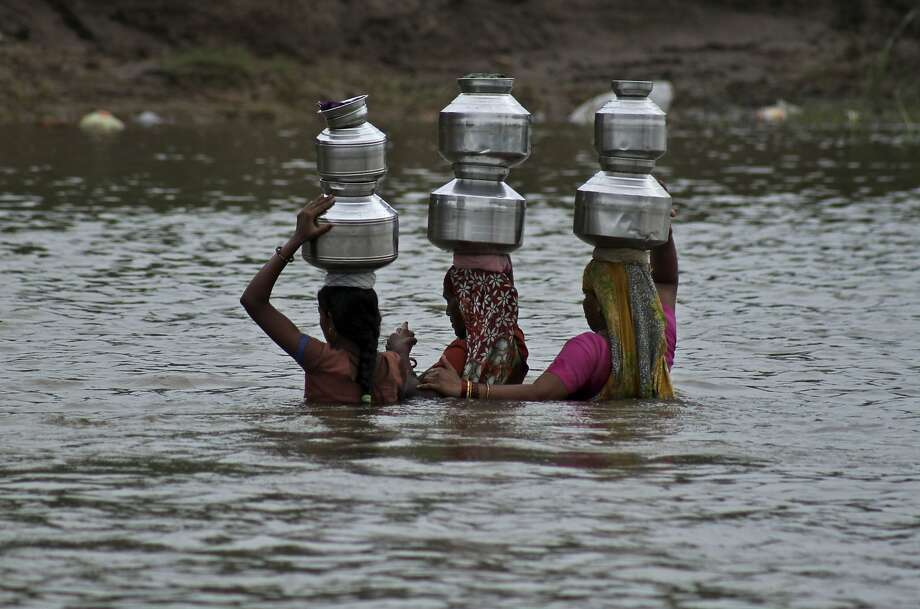 Imagine doing this every day for fresh water:Indian women hold each other for balance while crossing the River Heran with jugs of water on their heads near Sajanpura village, Gujarat state. The women of Sajanpura must cross the river 