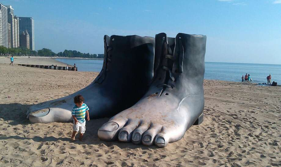 """A foothold on the beach:A boy reaches down to tickle the toes of a sculpture of a boot transforming into feet at North Avenue beach in Chicago. The sculpture was inspired by Rene Margritte's painting """"Le Modele Rouge."""" Photo: Antonio Perez, McClatchy-Tribune News Service"""